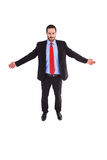 Unsmiling businessman standing with arms outstretched Royalty Free Stock Photo