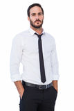 Unsmiling businessman standing with hands in pockets Stock Images