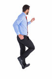 Unsmiling businessman in suit stepping Stock Photography