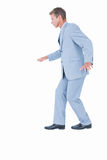 Unsmiling businessman in suit walking Stock Photo