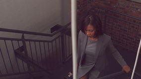 Unsmiling businesswoman going upstairs. In the office stock footage
