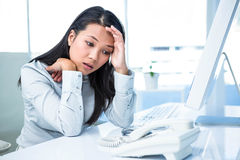 Unsmiling businesswoman with hands on face. In office royalty free stock images
