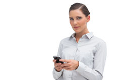 Unsmiling businesswoman holding cellphone Royalty Free Stock Photography