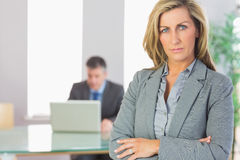 Unsmiling businesswoman looking at camera crossed arms with a bu. Unsmiling blonde businesswoman looking at camera crossed arms with a mature businessman working Stock Photos