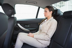 Unsmiling businesswoman sitting in the back seat Royalty Free Stock Photography