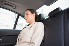 Unsmiling businesswoman sitting in the back seat Royalty Free Stock Images