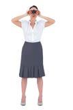 Unsmiling elegante Geschäftsfrau, die durch Ferngläser schaut Lizenzfreies Stockfoto
