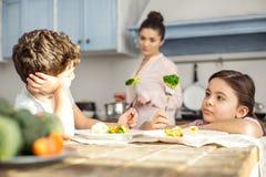 Unsmiling flicka och hennes broder som har grönsaker för frukost Arkivfoton