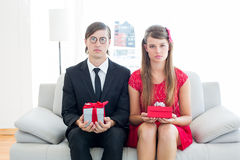 Unsmiling geeky couple with gift Royalty Free Stock Photo