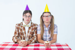 Unsmiling geeky hipsters celebrating birthday Royalty Free Stock Photography
