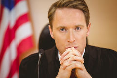 Unsmiling judge with american flag behind him Royalty Free Stock Images