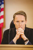 Unsmiling judge with american flag behind him Royalty Free Stock Photo