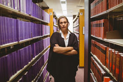 Unsmiling lawyer standing between shelfs with arms crossed Stock Photo