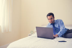 Unsmiling man lying on a bed using a laptop Royalty Free Stock Photo