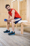 Unsmiling man sitting in locker room. At the gym Stock Photo