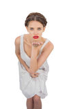 Unsmiling model in white dress blowing a kiss at camera Royalty Free Stock Photos
