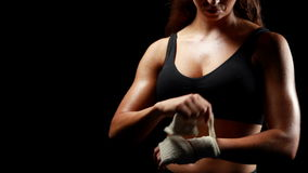 Unsmiling muscular woman wearing bandage. On black background stock video footage