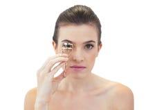 Unsmiling naturlig brun haired modell genom att använda ögonfranshårrullen Arkivfoton