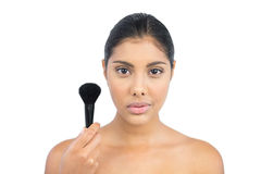 Unsmiling nude brunette holding powder brush Royalty Free Stock Photography