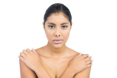 Unsmiling nude brunette holding shoulders Stock Image