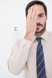 Unsmiling patient looking at camera with one eye Royalty Free Stock Image
