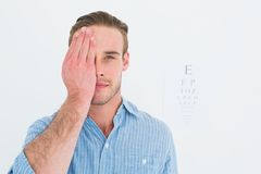 Unsmiling patient looking at camera with one eye. On white background Stock Photos