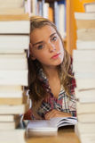 Unsmiling pretty student studying between piles of books Stock Images