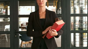Unsmiling woman with law code walking. In the office stock video