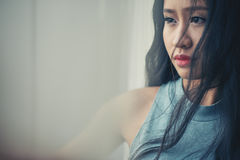 Unsmiling woman. Portrait of pensive unsmiling Vietnamese woman at window Royalty Free Stock Image