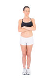 Unsmiling woman in sportswear crossing arms looking away Stock Photo