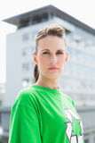Unsmiling woman wearing green shirt with recycling symbol Stock Photography