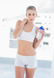 Unsmiling young blonde model holding a water bottle Stock Photography