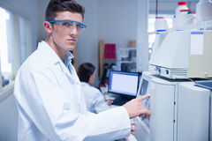 Unsmiling young chemist using the machine Stock Images