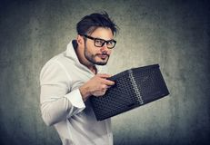 Greedy young man holding a box. Unsociable man holding a box and looking unwilling to share while posing on gray Royalty Free Stock Photo