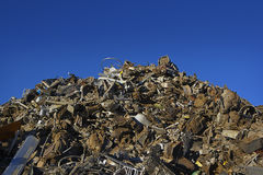 Unsorted Mountain of Scrap Metal. An unsorted mountain of scrap metal is waiting to be crushed in a recycle yard under bright blue skies Stock Photography