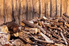 Unsorted wood pile against weathered wood-sided building. Large pile of various types of cut wood branches and logs, some with bark some not, is stacked against stock photography