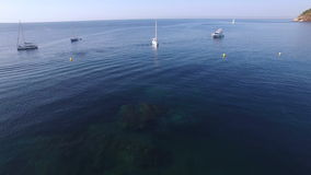 Unspoiled Mediterranean seaside beach aerial drone at sunrise. Aerial video shot in a typical Mediterranean beach landscape. Sailboats sailing in the bay at dawn stock video