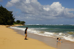 Unspoiled north shore beach in Oahu, Hawaii. Boy and Girl playing on unspoiled north shore beach in Oahu, Hawaii stock image