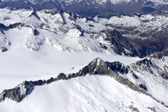 Unspoilt spring snows of  Adamello range, Italy. Aerial shot, from a small plane, of unspoilt snowy steep cliffs of Adamello range , shot  on a bright springtime Royalty Free Stock Image