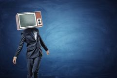 An unsteady businessman standing unevenly with a large retro TV on his head showing gray noise. Messy business. Scam and fraud. Unsure and lost royalty free stock photo