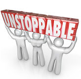 Unstoppable Team Lifting Word No Limits Determination. A team of three people lifts the word Unstoppable to illustrate the concept of determination and working Royalty Free Stock Images