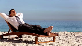 Unstressed businessman relaxing on the beach. On a deck chair stock footage