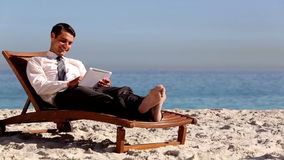 Unstressed businessman relaxing with a tablet pc. On a deck chair stock video footage