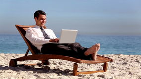 Unstressed businessman using laptop on the beach stock video footage