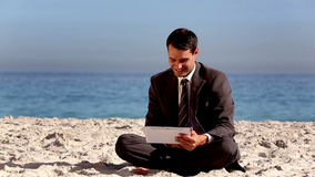 Unstressed businessman using tablet pc on the beach. During holidays stock video footage