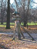 A wooden bird house in the park. An unsuaul tall bird house in the park with specific design stock photos