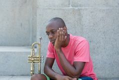 Unsuccessful african american artist with trumpet Stock Image