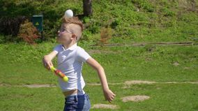 Unsuccessful attempt to hit a baseball ball. Boy play baseball and try to hit a flying ball. Child has a good time with friends on the nature in summer park stock video