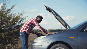 Unsuccessful car fixing. 4K Young stylish african guy having automobile problems and stranded roadside checks under the hood of his car stock video