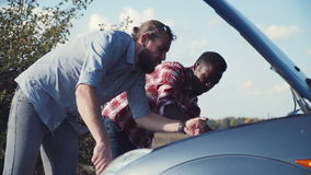 Unsuccessful car fixing. Two men trying to fix their car standing on roadside in countryside stock footage